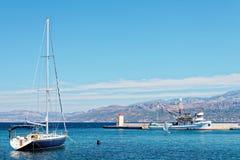 Förtöjd yatch och en fisketrålare i hamnen av en liten stad Postira - Kroatien, ö Brac Royaltyfri Bild
