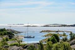 Förtöjde segelbåt och skerries i solen Arkivbilder