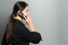 Förtegen affärskvinna som talar på hennes mobil Royaltyfri Foto