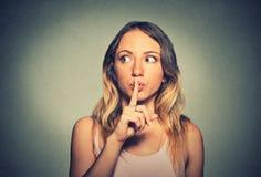 Förtegen kvinna som förlägger fingret på kanter som frågar shh, tystnad Arkivfoton