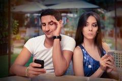 Förtegna par med Smart telefoner i deras händer Arkivbilder