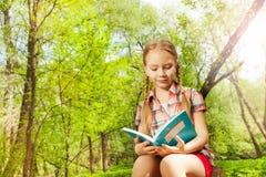 Förtjusande avkopplad flicka som läser en utomhus- bok Royaltyfri Foto