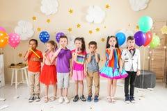 Förtjusande barn med partiblåsare inomhus royaltyfria bilder