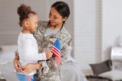 Förtjusande barn och hennes mamma som rymmer små flaggor Royaltyfria Foton