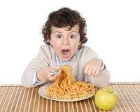Förtjusande barn som är hungrigt på tiden av att äta arkivfoto