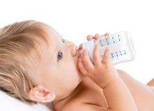 Förtjusande barn som dricker från flaskan Arkivbilder