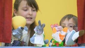 Förtjusande barn som spelar med handleksaker på dockteaterföreställning arkivfilmer