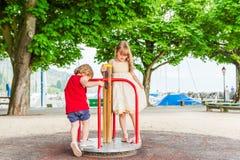Förtjusande barn som spelar på lekplats Arkivbild