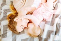 Förtjusande behandla som ett barn flickan som kysser hennes lyckliga moder Royaltyfria Foton