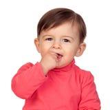Förtjusande behandla som ett barn flickan med henne handen i mun Arkivfoton