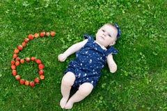 Förtjusande behandla som ett barn flickan på gräs med jordgubbar sex malar Arkivfoto