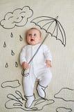 Förtjusande behandla som ett barn flickan som skissas som det hållande paraplyet royaltyfri foto