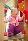 Förtjusande behandla som ett barn klättringen för att behandla som ett barn glidbanan på lekplats 免版税图库摄影