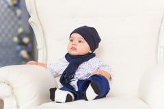 Förtjusande behandla som ett barn pojken i rummet Nyfött barn som kopplar av på soffan Barnkammare för unga barn Hemmastadd famil Arkivbild