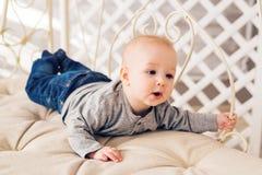Förtjusande behandla som ett barn pojken i soligt sovrum Koppla av för nyfött barn Barnkammare för unga barn Hemmastadd familjmor Royaltyfri Foto