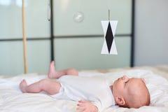 Förtjusande behandla som ett barn pojken i vita soliga sovrumligga och blickar på den Munari Montessori mobilen royaltyfri foto