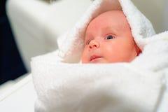 Förtjusande behandla som ett barn pojken som ut ser under den vita handduken Fotografering för Bildbyråer