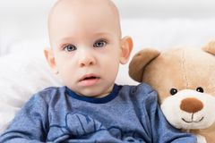 Förtjusande behandla som ett barn pojkesammanträde på en säng som spelar med leksakbjörnar på en säng Stående för nyfött barn royaltyfri fotografi