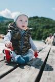 Förtjusande behandla som ett barn pojkesammanträde utomhus på ett wood däck Royaltyfri Foto