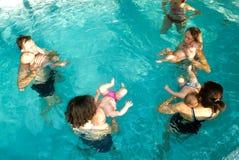 Förtjusande behandla som ett barn tycka om att simma i en pöl med hans moder Royaltyfria Foton