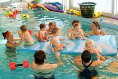 Förtjusande behandla som ett barn tycka om att simma i en pöl med hans moder Arkivfoton