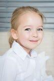 Förtjusande blond förskole- flickastående som ler barnet royaltyfri fotografi