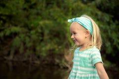Förtjusande blond flicka som har roligt utomhus Arkivfoton