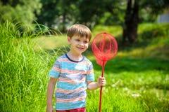 Förtjusande Caucasian unge som spelar med skopa-netto på ängen på varm och solig sommar eller vårdag royaltyfri foto