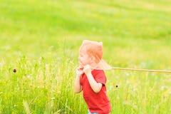 Förtjusande Caucasian unge som spelar med skopa-netto på ängen på varm och solig sommar eller vårdag arkivfoto