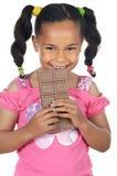 förtjusande choklad som äter flickan arkivbild