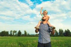 Förtjusande dotter- och faderstående, lyckligt familjbegrepp royaltyfri foto