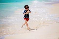 Förtjusande förskole- barn, pojkar och att ha gyckel på havstranden Upphetsade barn som spelar med vågor, simning som lyckligt pl fotografering för bildbyråer
