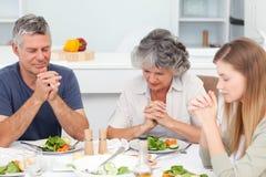 Förtjusande familj som ber på tabellen arkivbilder