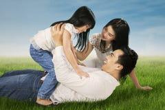 Förtjusande familj som spelar på ängen Fotografering för Bildbyråer