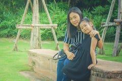 Förtjusande familjbegrepp: Den asiatiska kvinnan och barn som ler och sitter, kopplar av på konkret lång bänk på offentligt parke Arkivfoton