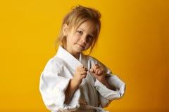 Förtjusande flicka i kimono på gul bakgrund arkivbilder