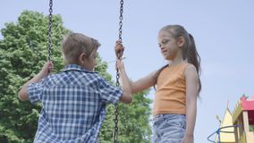 Förtjusande flicka med långt hår som utomhus svänger på en gullig pojke för gunga Par av lyckliga barn Roliga bekymmerslösa ungar arkivfilmer