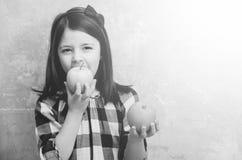 Förtjusande flicka som äter det gröna äpplet med apelsinen i hand royaltyfri fotografi