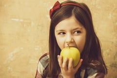 Förtjusande flicka som äter det gula äpplet för vitamin royaltyfria bilder