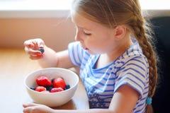 Förtjusande flicka som äter nya bär Fotografering för Bildbyråer