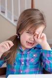 Förtjusande flicka som gråter och torkar hennes öga arkivfoto