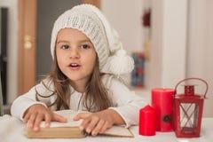 Förtjusande flicka som läser en bok och väntar på Santa Claus royaltyfria foton