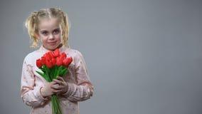 Förtjusande flicka som luktar blommor och ler på grå bakgrund, ferielynne arkivfilmer