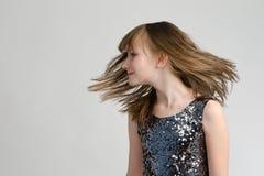 Förtjusande flicka som skakar henne som är head med långt hår Royaltyfri Bild