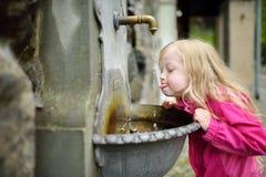 Förtjusande flicka som spelar med dricksvattenspringbrunnen i Lindau, Tyskland arkivbilder