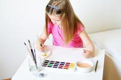 Förtjusande flickamålning med vattenfärgen i ett soligt vitt rum på Arkivbild