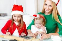 Förtjusande flickor med henne stekheta julkakor för moder i Ket arkivbilder