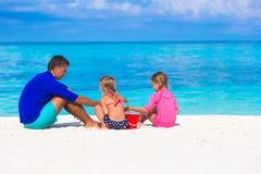 Förtjusande flickor och lycklig fader som spelar med stranden Royaltyfri Foto