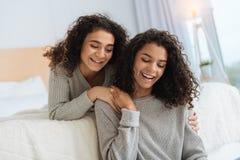 Förtjusande flickor som ler, medan ligga på säng och att prata arkivfoto
