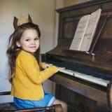 Förtjusande gullig flicka som spelar pianobegrepp Arkivfoton